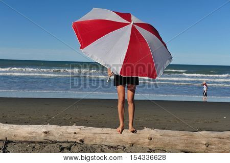 Young fit woman stands covering her face under colorful parasol on a sandy beach.