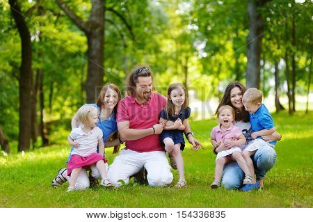 Happy big family of three adults and four kids having fun in summer park
