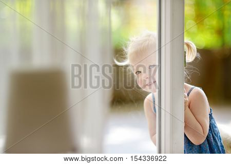 Cute Little Toddler Girl Peeking Into A Window