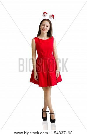 Portrait of a smiling brunette girl on white studio shot in a Santa Claus hat and red dress. rabbit ear