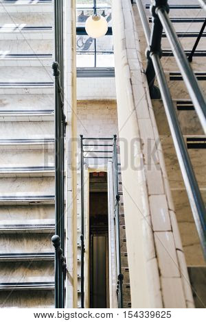Stairwell Of An Ancient Marble Staircase With Window And Lamp