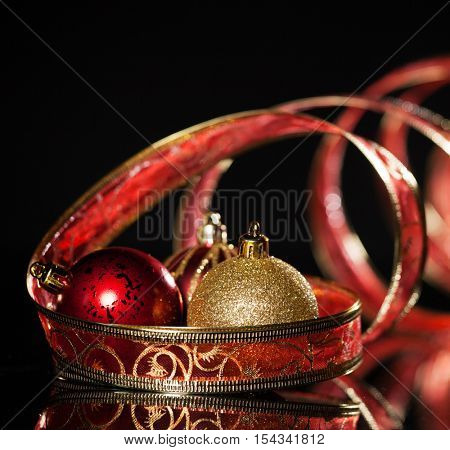 Gold christmas sphere with ribbon on black background. Christmas decoration. Celebration