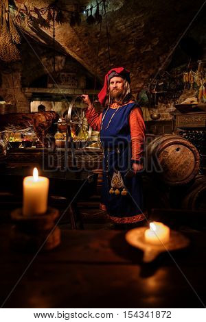 Medieval man doing roasted pig on the rack in ancient castle kitchen.
