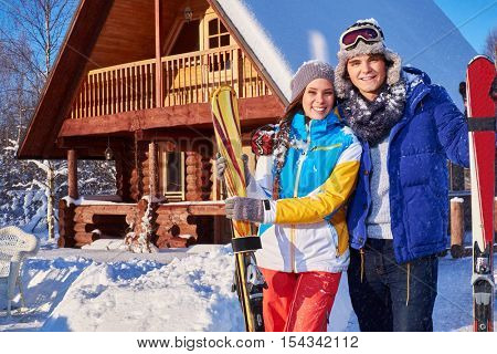 Cheerful couple spend winter holidays at mountain cottage
