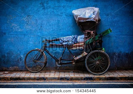 DELHI, INDIA - SEPTEMBER 11, 2011: Indian cycle rickshaw driver sleeps on his bicycle in street of New Delhi. Cycle rickshaws are used in India from about 1930 and now common in rural and urban areas.