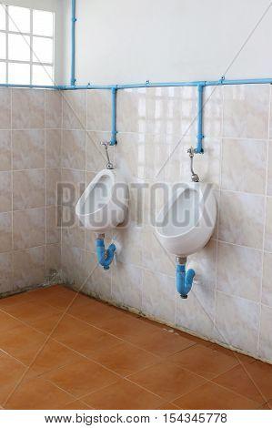 The white urinals in public men's bathroom.