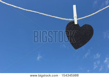 Black Heart hung on hemp rope on blue sky background and have copy space to manage the text you want.