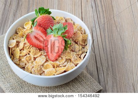 Cereal Conr flakes with strawberry on wood backgound