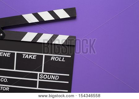 movie clapper on violet background, top view