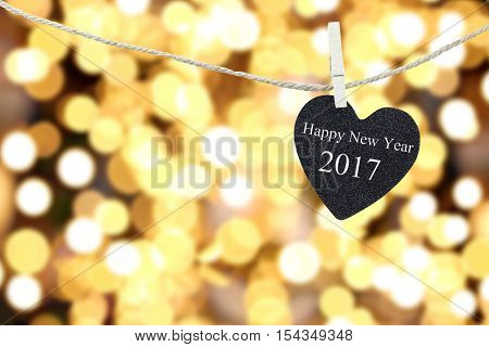Black Heart hung on hemp rope on bokeh a golden color background and have white color of Happy new year 2017 text.