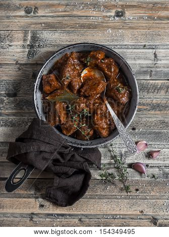 Braised beef in a frying pan on a wooden rustic table. Top view