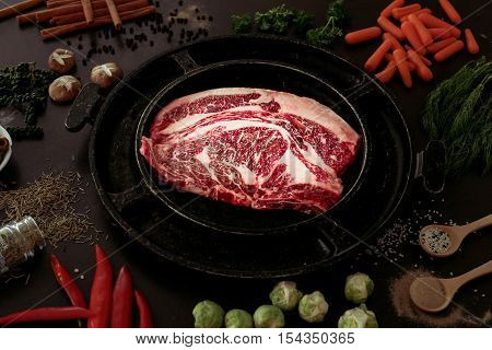 Ingredients for cooking healthy meat dinner. Raw uncooked beef rib eye steaks with vegetables rice herbs and spices on table background cast iron grilling pan in center