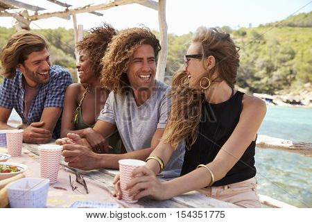 Four friends at a table by the sea, looking away, close up
