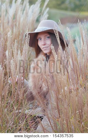 Woman in beige fur coat and felt fedora hat in the dry autumn field selective focus.