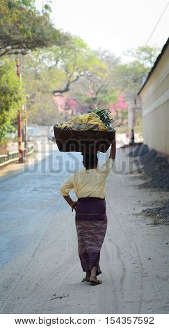 Burmese Woman Carrying A Bag On Her Head
