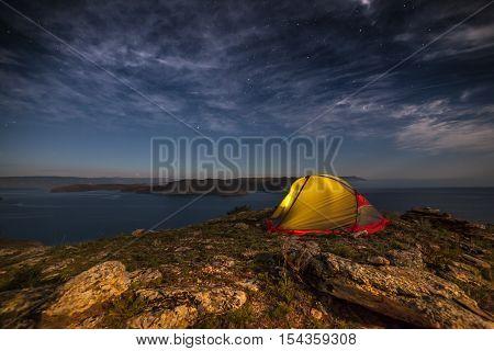 Iluminated tent against mountain at moon night on rocks