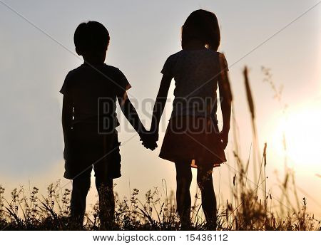 Two children, male and female standing against the sun, sunset, romance