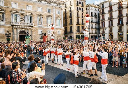 Barcelona Spain - May 29 2016: The Castellers de Barcelona of the Corpus Christi festival stand in front of the historical town hall with Giant puppets Gigantes and viewers.