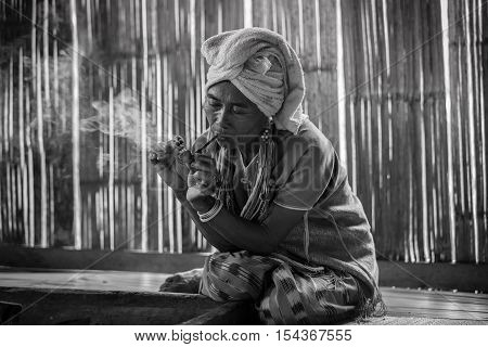 Female karen hill tribe is smoking tobacco pipe traditional in the cottage of northern Thailand at Mae Klang Luang Mae Chaem Chiang Mai Province. Black and white picture style