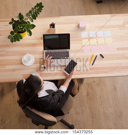 Top view of pregnant business woman sitting at table in front of laptop computer and holding mobile or smart phone. All screens are blank for your ideas, desires or memories.