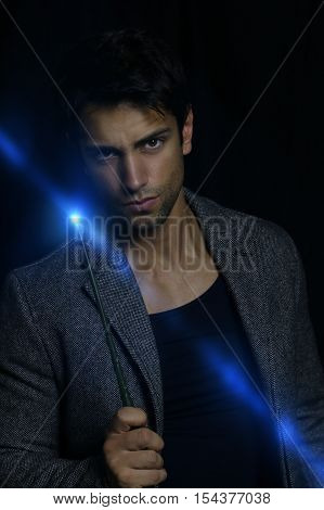 young wizard holding a magic wand over a black background