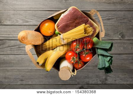 Full paper bag of different groceries on wooden background top view
