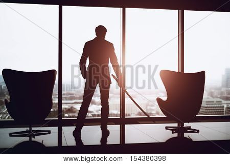 Businessman in office in business suit standing between of two armchairs next to window and holding katana sword like japanese samurai warrior blurred winter city top view in background