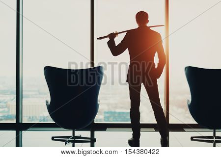 Young businessman in office in business suit standing between of two armchairs in front of window and holding katana sword like japanese samurai warrior blurred winter city top view in background