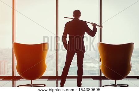 Businessman in office in business suit standing between of two armchairs in front of window and holding katana sword like japanese samurai warrior blurred winter city top view in background