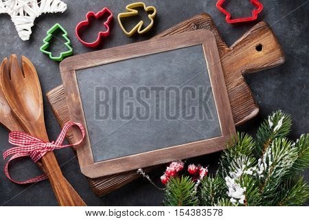 Christmas cooking utensils and snow tree on stone table. Top view with chalk board copy space for your text