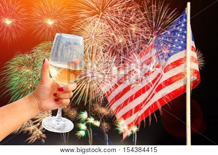 Woman holding a wine glass celebratory fireworks on the background of the US flag Independence day Congratulated the winner of the US presidential election.