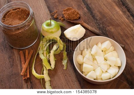 Ingredients for homemade apple sauce with peeled and diced fresh green cooking apples stick cinnamon and aromatic ground spice for seasoning on a wooden table