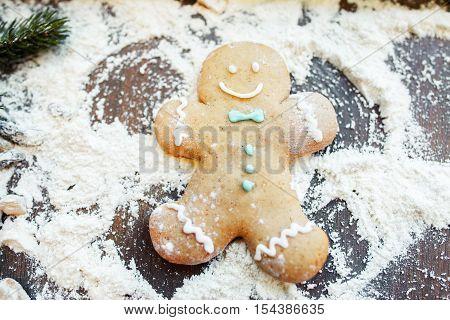 Gingerbread man making snow angel on flour. Fun at kitchen, cooking art, Christmas treat preparing
