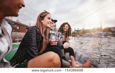 Shot of group of happy young people relaxing by the lake and having drinks. Teenage friends sitting on jetty and smiling.