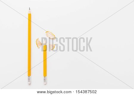 Long and short pencils with shavings on white background, free space for text or advertisement. Top view on two wood pencils with wooden flakes. Chancellery, art, drawing materials, design concept