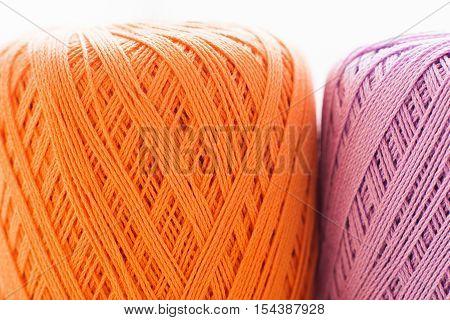 Orange and purple knitting thread background. Bright handiwork backdrop, colorful crochet string, Leisure, hobby, needlework concept