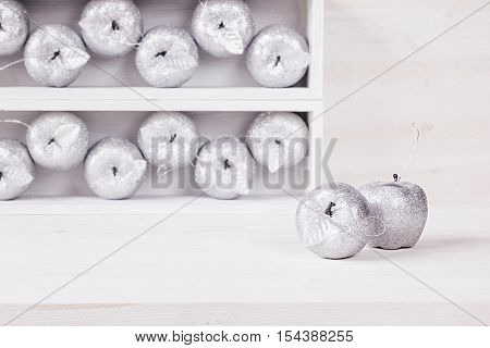 Christmas home soft decor of silver apples in boxes on wooden white background. Xmas background.