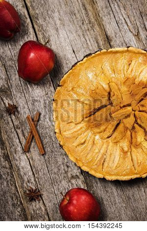 Homemade apple tart with honey and lemon filling on rough wooden background with apples and cinnamon sticks. Selective focus