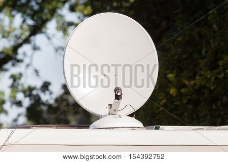 Satellite dish with sky on roof of camper van