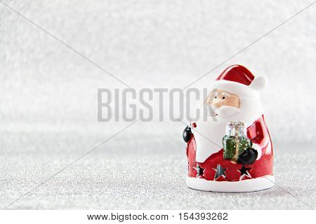 Merry Christmas or Happy New Year concept : Cute santa claus doll on silver glitter paper background