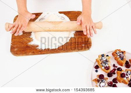 Rolling out dough, pastry cooking, free space. Top view on hands with pin and duff, sweet cakes with berries in corner. Homemade bakery, children culinary, sweet making concept