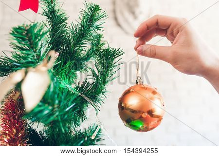 Close-up of hand with golden decorating ball. Christmas tree, winter holiday celebration, happy family party concept