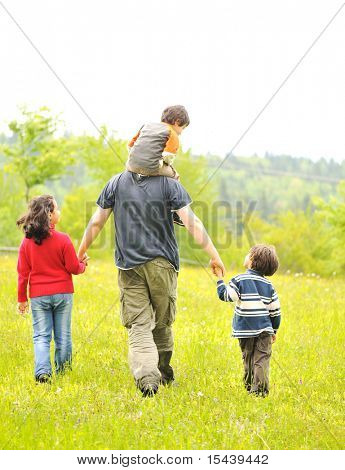 happy family in nature, father and children walking