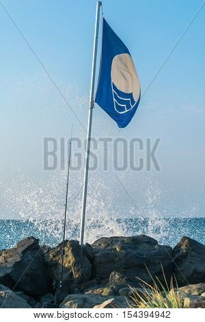 Blue Flag against blue sky. Blue Flag is an international award given to beaches that meet excellence in the areas of safety, cleanliness and environmental standards