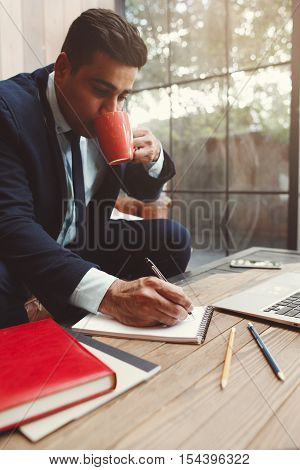 Office employee doing work at office. Businessman having coffee break while working. Hardworking, workaholism and overwork concept.