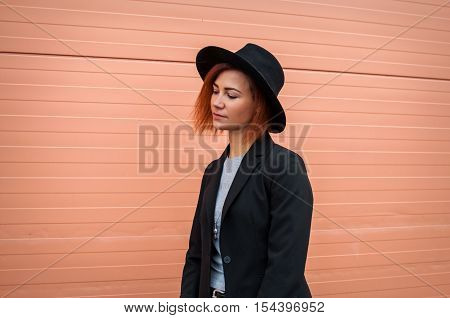 Attractive vogue model alluring outdoor by the pink wall. City style. Fashion photo