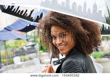 Ethnic girl in the street with umbrella on rainy day