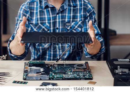 Laptop disassembling at electronic repair shop. Unrecognizable engineer separating computer from case. Electronic renovation, business, occupation concept