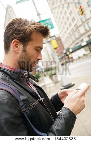 Tourist in New york city looking at city guide on smartphone