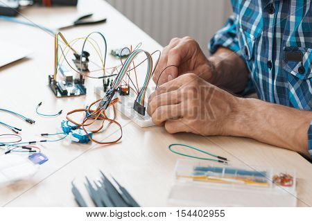 Breadboard with connected cables close-up. Engineer creating electronic construction. Modern technologies, electronics, diy product engineering